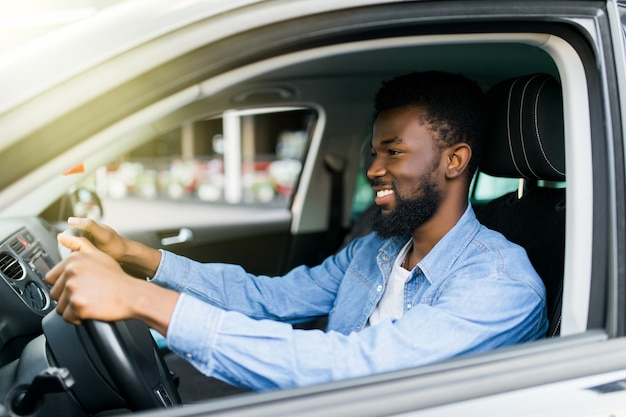 Gelukkig jonge afro-amerikaanse man autorijden op straatwegen