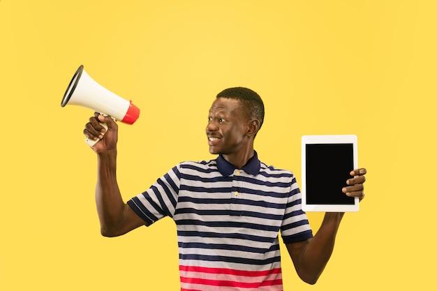 Gelukkig jonge afro-amerikaanse man met tablet geïsoleerd op gele studio achtergrond