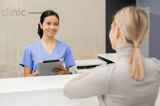 Gelukkig jonge assistent met tablet staan bij receptie balie voor patiënt tijdens het registreren van haar in klinieken