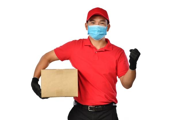 Gelukkig jonge aziatische bezorger in rood uniform, medisch gezichtsmasker, beschermende handschoenen dragen kartonnen doos in handen geïsoleerd op wit. bezorger geeft pakketverzending. veilige levering