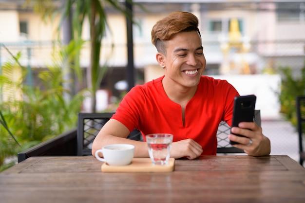 Gelukkig jonge aziatische man met behulp van telefoon in de coffeeshop buitenshuis