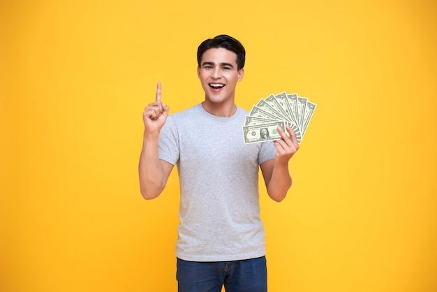 Gelukkig jonge aziatische man met dollar geld en wijzende vinger naar geïsoleerd op gele achtergrond.