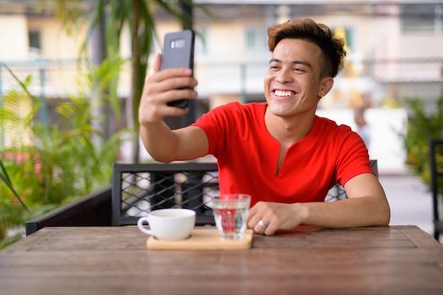 Gelukkig jonge aziatische man selfie te nemen bij de coffeeshop buitenshuis