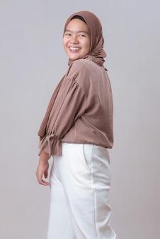Gelukkig jonge aziatische moslim model vrouw in hijab glimlachend poseren geïsoleerd op een grijze achtergrond