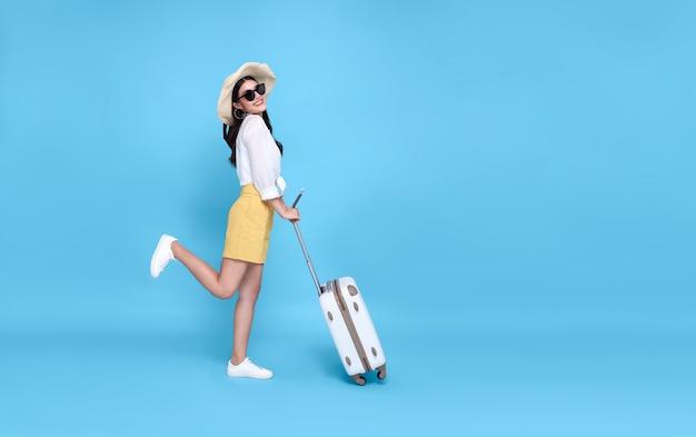 Gelukkig jonge aziatische toeristische vrouw met paspoort en instapkaart met bagage gaan reizen op vakantie geïsoleerd op blauw.
