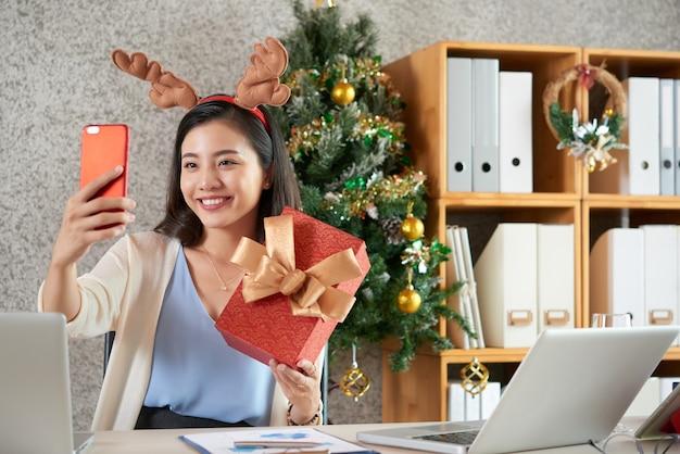 Gelukkig jonge aziatische vrouw in rendieren haarband selfie met kerstcadeau te nemen