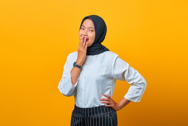 Gelukkig jonge aziatische vrouw lachen en bedekken mond met hand geïsoleerd op gele achtergrond