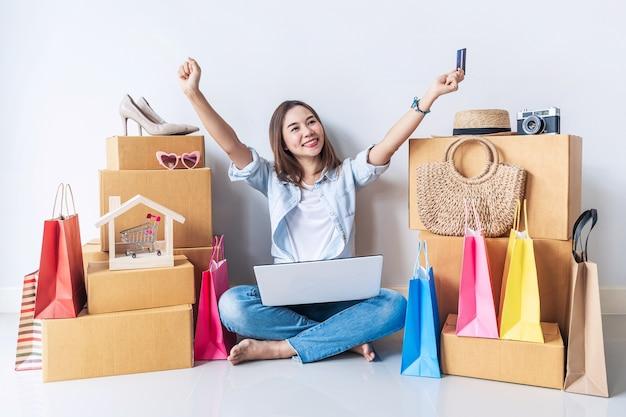 Gelukkig jonge aziatische vrouw met kleurrijke boodschappentas en stapel kartonnen dozen thuis