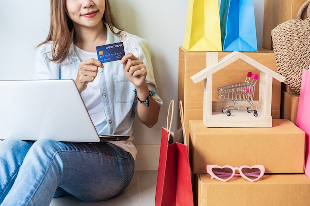 Gelukkig jonge aziatische vrouw met kleurrijke boodschappentas, mode artikelen en stapel kartonnen dozen thuis
