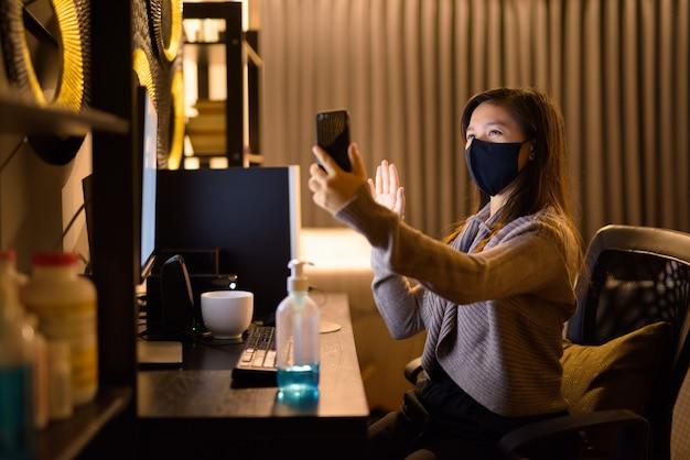 Gelukkig jonge aziatische vrouw met masker videobellen tijdens het werken vanuit huis 's nachts
