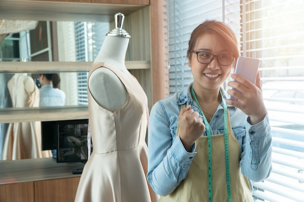 Gelukkig jonge aziatische vrouw naaister modeontwerper gebruikt een smartphone