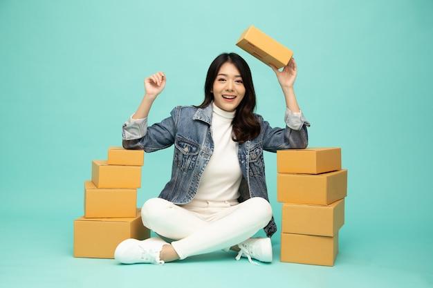 Gelukkig jonge aziatische vrouw opstarten kleine bedrijven freelance zittend op de vloer met pakketdoos en geïsoleerd op groene achtergrond, online marketing verpakkingsdoos leveringsconcept
