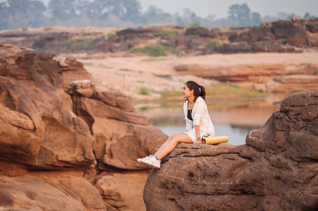 Gelukkig jonge aziatische vrouw reiziger met papieren kaart op rots klif in de grand canyon van thailand