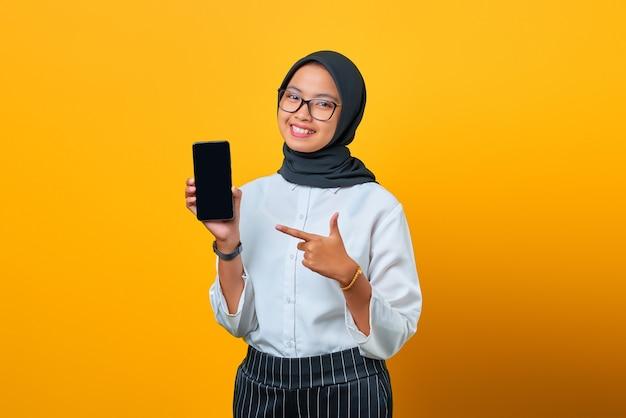 Gelukkig jonge aziatische vrouw wijzend op het lege scherm van de mobiele telefoon geïsoleerd op gele achtergrond