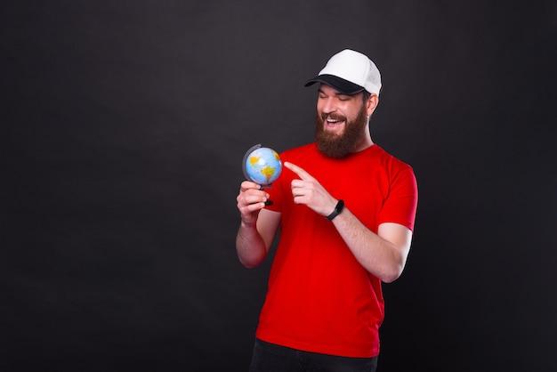 Gelukkig jonge bebaarde hipster man wijzend op de volgende bestemming op wereldbol