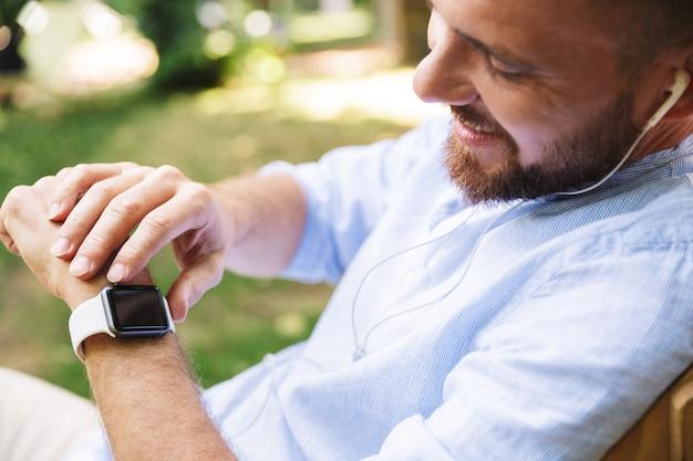 Gelukkig jonge bebaarde man buitenshuis luisteren muziek met horloge.