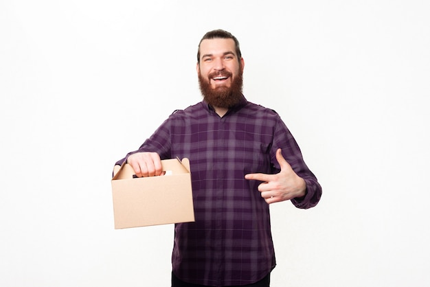 Gelukkig jonge bebaarde man glimlachend en wijzend op lunchdoos