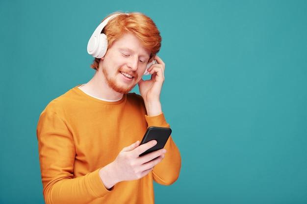 Gelukkig jonge bebaarde man met brede glimlach, luisteren naar muziek in hoofdtelefoons en scrollen door afspeellijst in smartphone