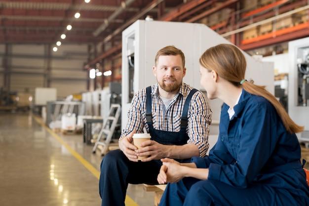 Gelukkig jonge bebaarde man met warme drank praten met zijn collega tijdens de koffiepauze zittend in de werkplaats