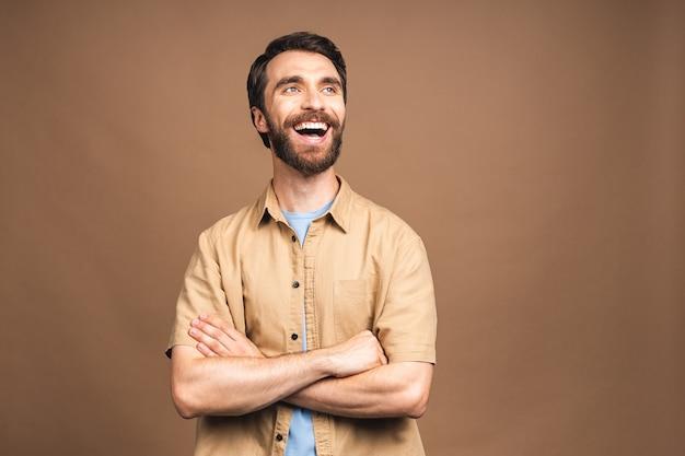 Gelukkig jonge, bebaarde man. portret van een knappe jongeman in casual die zijn armen gekruist houdt en glimlacht terwijl hij tegen een beige achtergrond staat.