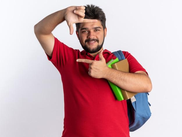 Gelukkig jonge bebaarde student man in rood poloshirt met rugzak met notebooks maken frame met vingers door vingers glimlachend vrolijk staande over witte muur