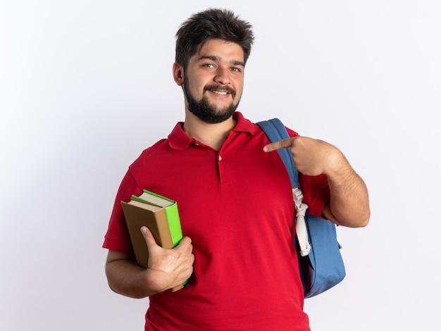 Gelukkig jonge, bebaarde student man in rood poloshirt met rugzak met notebooks wijzend met wijsvingers naar notebooks glimlachend vrolijk staande