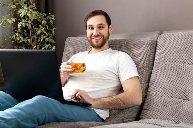Gelukkig jonge blanke man drinkt thee tijdens het werken vanuit huis met behulp van laptop. gezellig thuiskantoor,