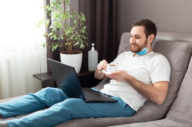 Gelukkig jonge blanke man in medische gezichtsmasker thee drinken tijdens het werken vanuit huis met behulp van laptop