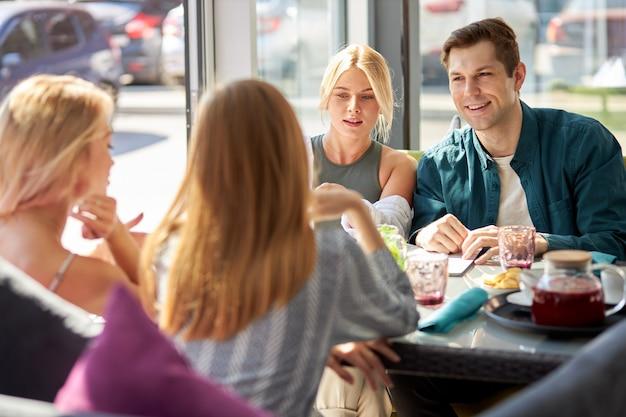 Gelukkig jonge blanke vrienden verzamelen in café
