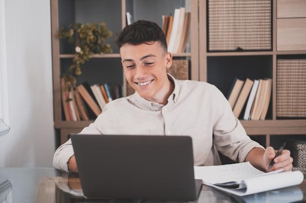 Gelukkig jonge blanke zakenman glimlachend online werken kijken naar webinar podcast op laptop en leren onderwijs cursus conferentiegesprekken maken aantekeningen zitten op het werk bureau, e-learning concept