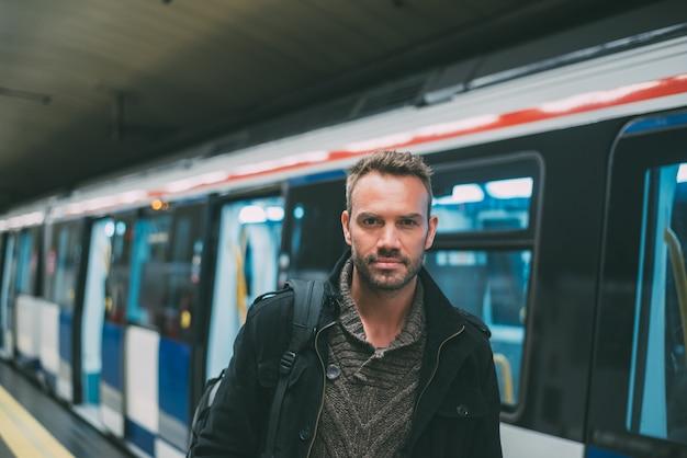 Gelukkig jonge blonde man met backpacken in het metrostation te wachten op de trein