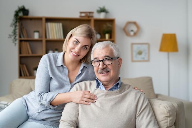Gelukkig jonge blonde vrouw en haar vader in vrijetijdskleding ontspannen op de bank in de thuisomgeving voor camera