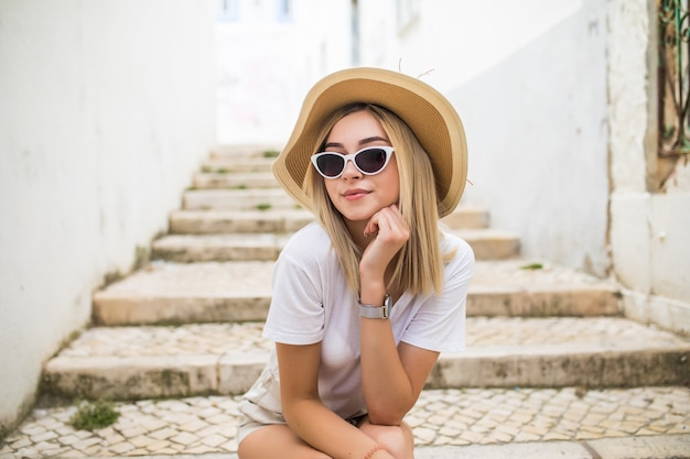 Gelukkig jonge blonde vrouw in hoed en zonnebril lachen