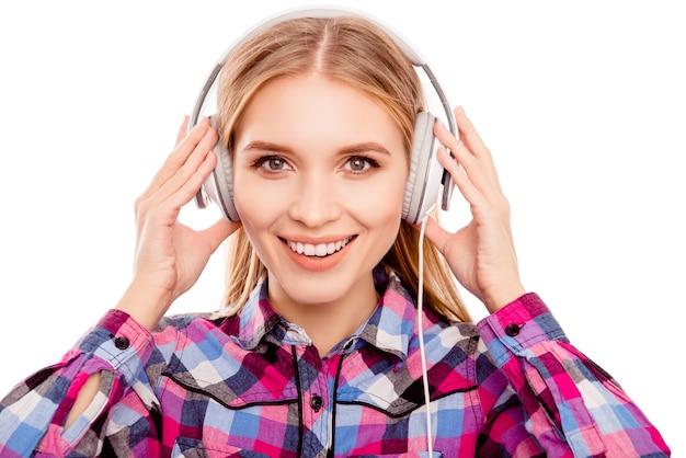 Gelukkig jonge blonde vrouw luisteren muziek met een koptelefoon