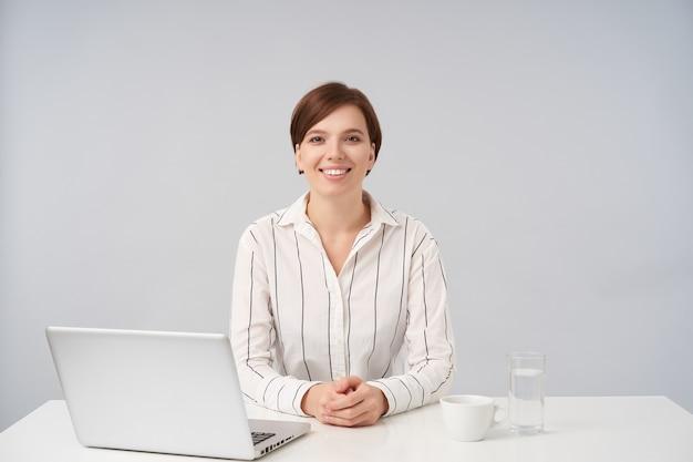 Gelukkig jonge bruinogige charmante kortharige brunette dame houdt haar handen op het aanrecht zittend aan tafel op wit, vrolijk op zoek met een brede glimlach