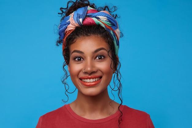 Gelukkig jonge bruinogige mooie brunette krullende vrouw met feestelijke make-up vrolijk op zoek naar voorzijde met brede glimlach, geïsoleerd over blauwe muur in casual t-shirt