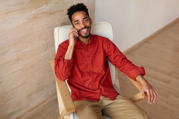 Gelukkig jonge brunette bebaarde donkere man gekleed in vrijetijdskleding kijken graag met aangename glimlach terwijl het hebben van telefoongesprek, geïsoleerd op interieur