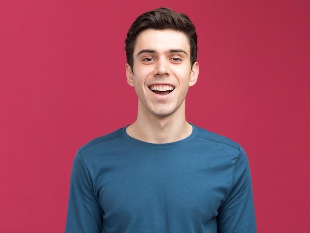 Gelukkig jonge brunette blanke man geïsoleerd op roze muur met kopie ruimte