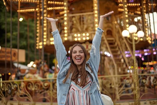 Gelukkig jonge brunette dame met lang haar permanent over carrousel in park van attracties, handen vreugdevol verhogen met brede mond geopend, positieve emoties concept