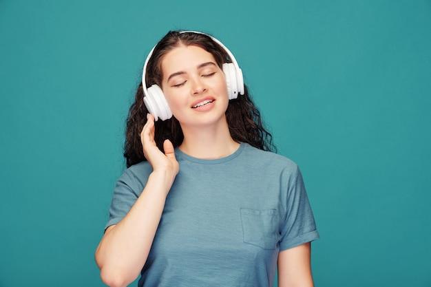 Gelukkig jonge brunette vrouw in blauw t-shirt en witte koptelefoon genieten van ontspannende muziek