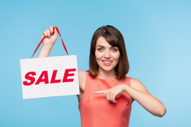 Gelukkig jonge brunette vrouw in rode jurk wijzend op verkoopaankondiging in haar hand terwijl ze u uitnodigt om iets te kopen