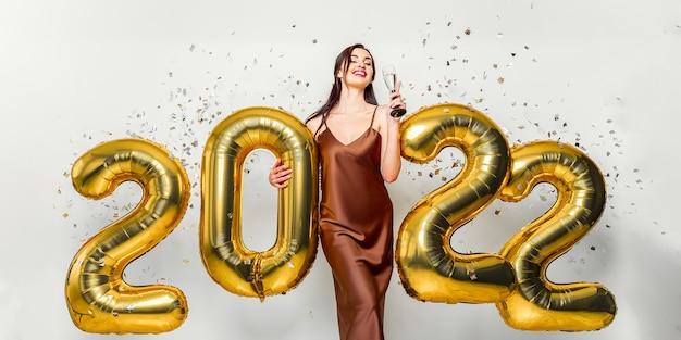 Gelukkig jonge brunette vrouw met glas champagne in de buurt van gouden ballonnen op witte achtergrond met cl...