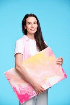 Gelukkig jonge brunette vrouw met kunstwerk terwijl je in isolatie blauwe muur