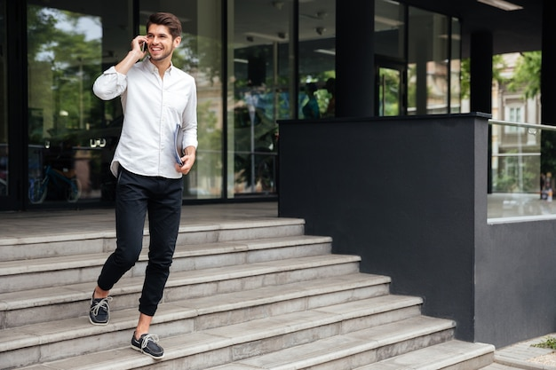Gelukkig jonge buinessman met mappen lopend en pratend op mobiele telefoon buitenshuis