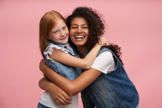 Gelukkig jonge dames met lang haar glimlachend oprecht terwijl ze elkaar omhelzen, genieten van tijd samen terwijl poseren op roze in casual kleding
