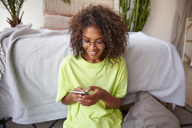 Gelukkig jonge donkere gekrulde vrouw smartphone in handen houden, haar sociale netwerken controleren, scherm kijken en glimlachen, poseren over interieur