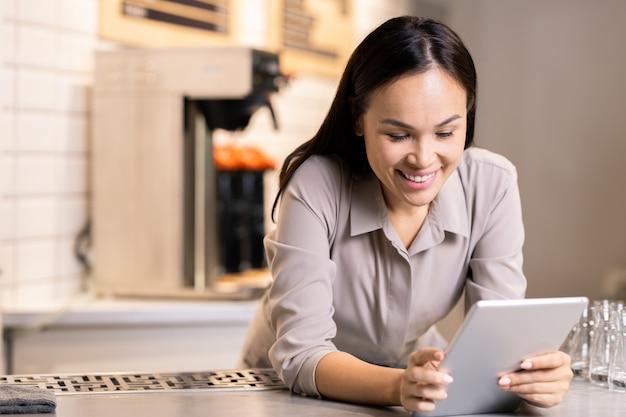Gelukkig jonge eigenaar van luxe restaurant met behulp van digitale tablet tijdens het zoeken via menu of online bestellingen van klanten