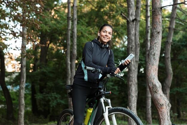 Gelukkig jonge fitness vrouw rijden op een fiets in het park, luisteren naar muziek met koptelefoon, mobiele telefoon houden