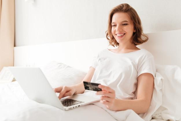 Gelukkig jonge geweldige vrouw zitten binnenshuis met behulp van laptop