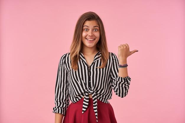 Gelukkig jonge groenogige bruinharige vrouw met casual kapsel vrolijk glimlachend en opzij tonen met duim, staande tegen roze in feestelijke kleding
